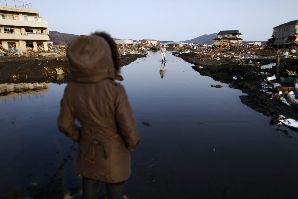 Earthquake and tsunami survivors walk through a flooded street searching for their belongings in the destroyed residential area of Kesennuma
