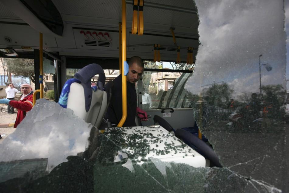 An Israeli police officer surveys the inside of a damaged bus at the scene of an explosion in Jerusalem
