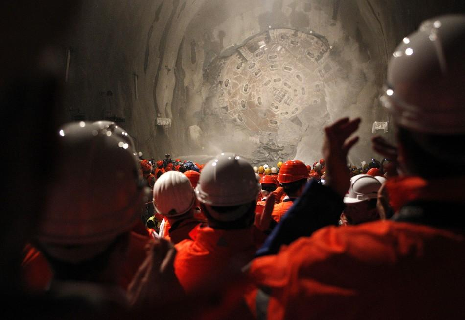 """Miners watch as the drill machine """"Sissi"""" breaks through the rock at the final section Faido-Sedrun construction site of the NEAT Gotthard Base Tunnel"""
