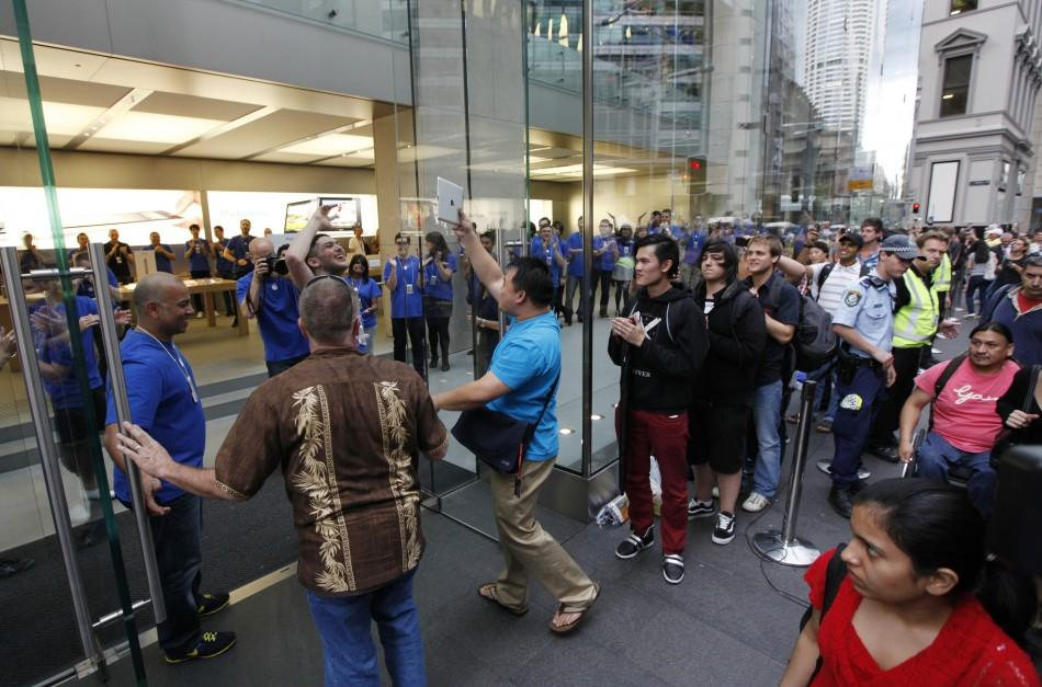 Apple store staff in Sydney welcome first shopper, Lee of Canada, the moment Apple's iPad 2 became available for direct purchase in Australia