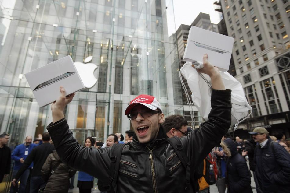 A customer holds up a pair of Apple's iPad 2 tablet after purchasing the second generation device at the Apple's flagship 5th Ave store in New York