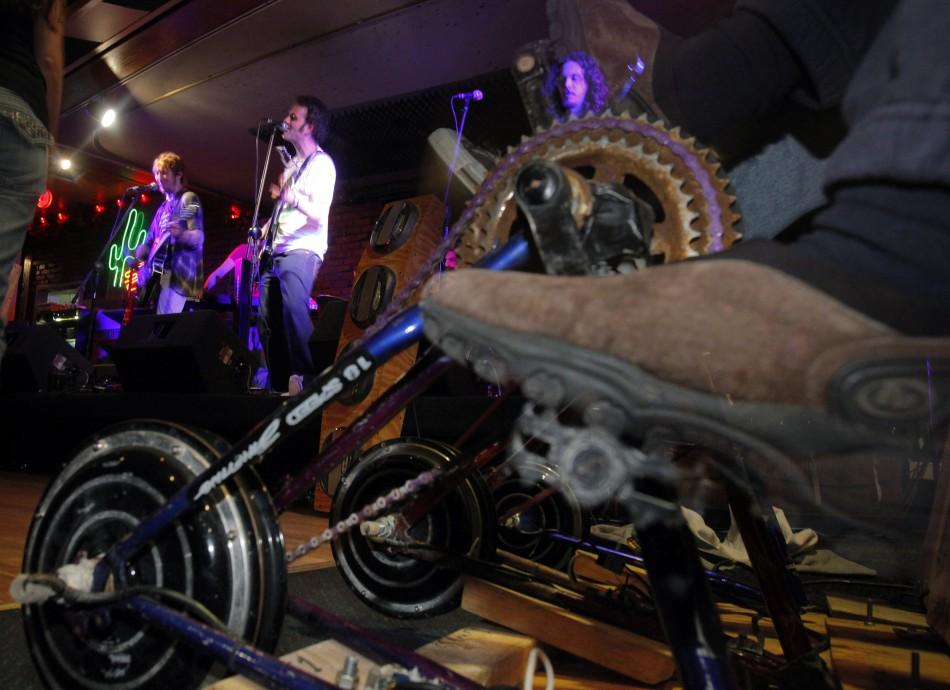 "Members of the audience pedal the ""Sustainable Sound"" system, an eco friendly power generator, during a band performance in Somerville"