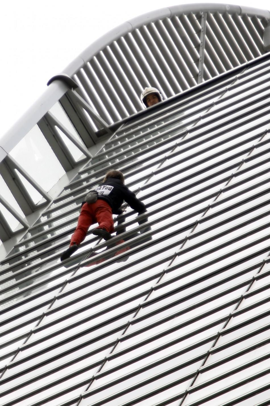 French climber Alain Robert scales the 185 metre GDF Suez Tower at the La Defense business district