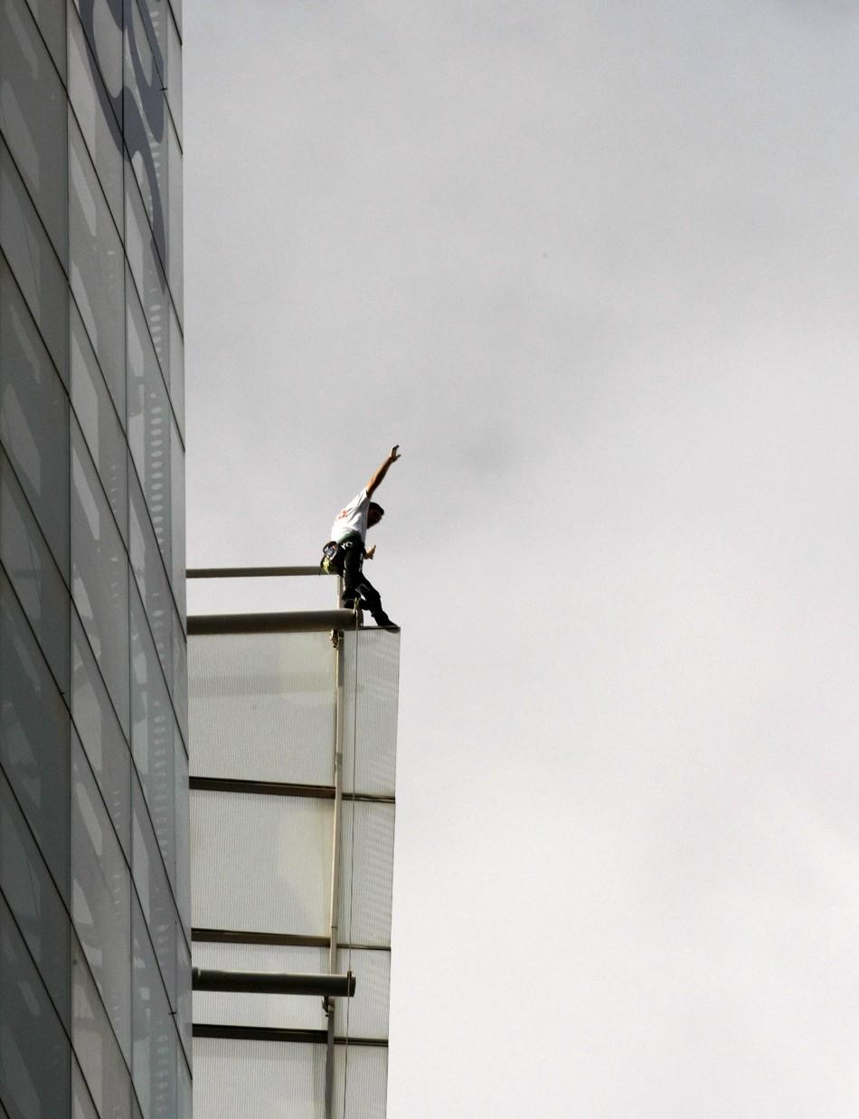 French climber Robert waves from the top of the 41-storey Aurora Place office tower in central Sydney