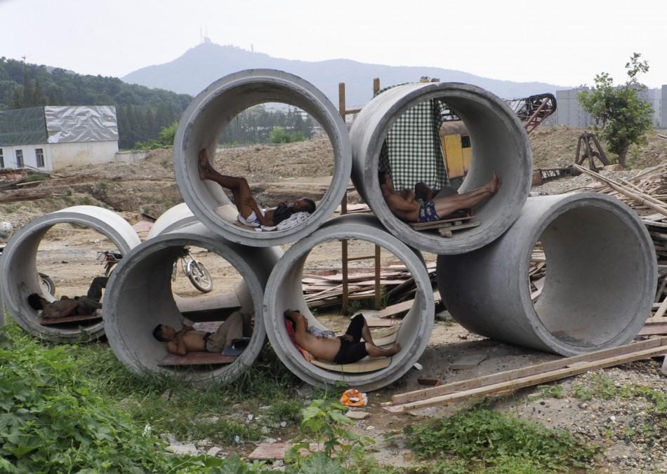Migrant workers nap inside cement pipes at a construction site in Xiangfan