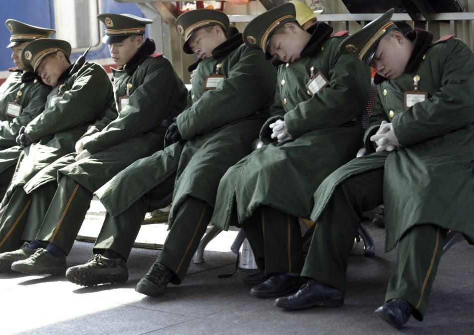 Paramilitary policemen sleep at a platform of the Guangzhou railway station