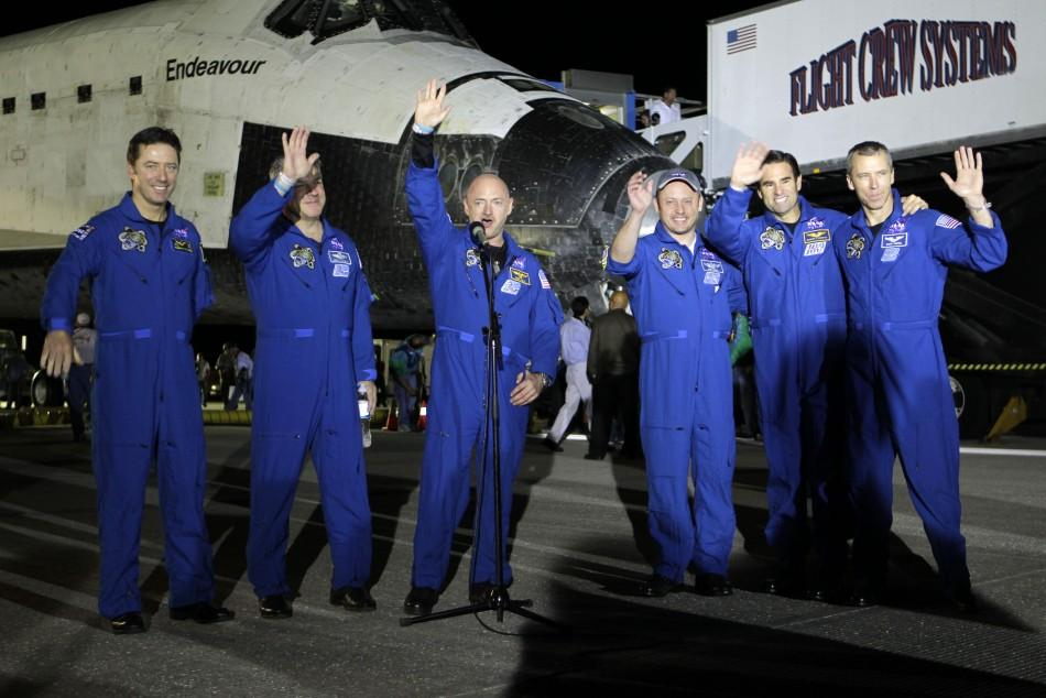 The crew of space shuttle Endeavour wave after landing in Cape Canaveral
