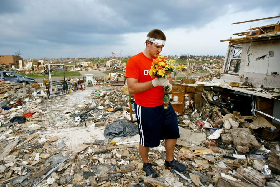 Volunteer Nelson Rumsey, of Quincy, Il., collects plastic flowers from a house destroyed by the May 22 tornado in Joplin