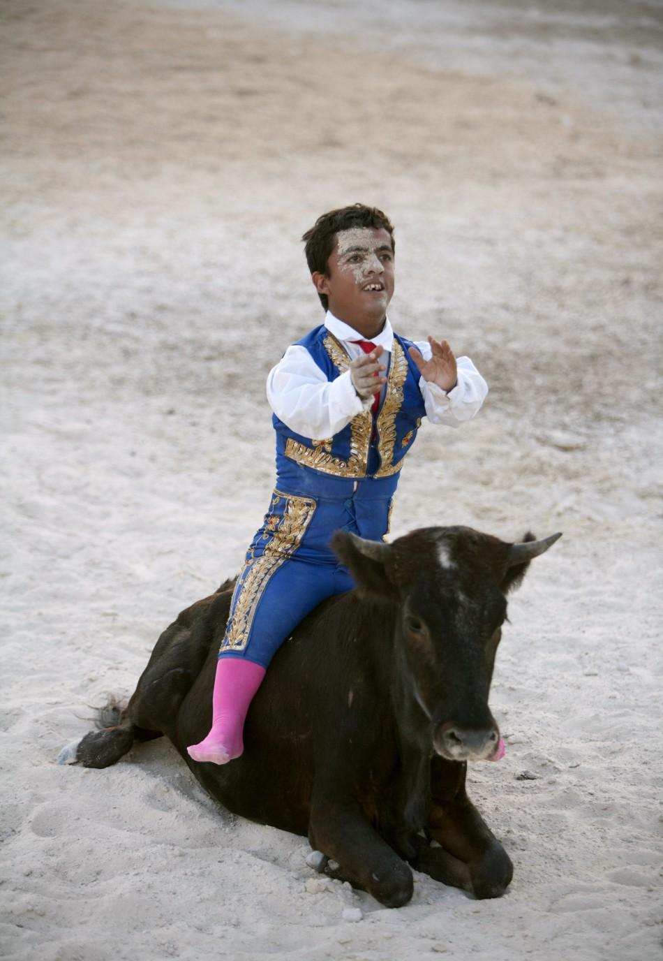 Dwarf bullfighter Jorge Vega from Los Enanitos Toreros sits on a calf at the end of a presentation in Cancun