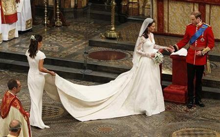 Maid of Honour, Pippa Middleton (L) holds the wedding dress of her sister Catherine, Duchess of Cambridge, after her she married Britain's Prince William
