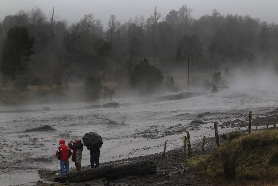 Residents watch as steam rises from the Nilhue River, fed by unusually warm water from the hot flanks of an erupting volcano from the Puyehue-Cordon Caulle volcanic chain, near Lago Ranco town