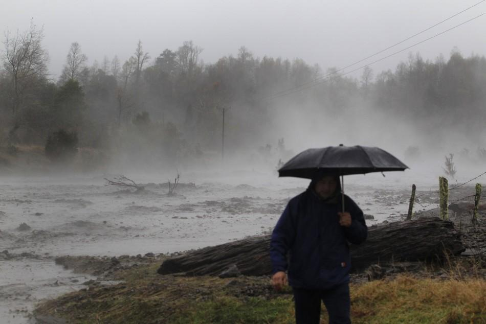 Steam rises from the Nilhue River, fed by unusually warm water from the hot flanks of an erupting volcano from the Puyehue-Cordon Caulle volcanic chain, as a resident walks on the river bank near Lago Ranco town