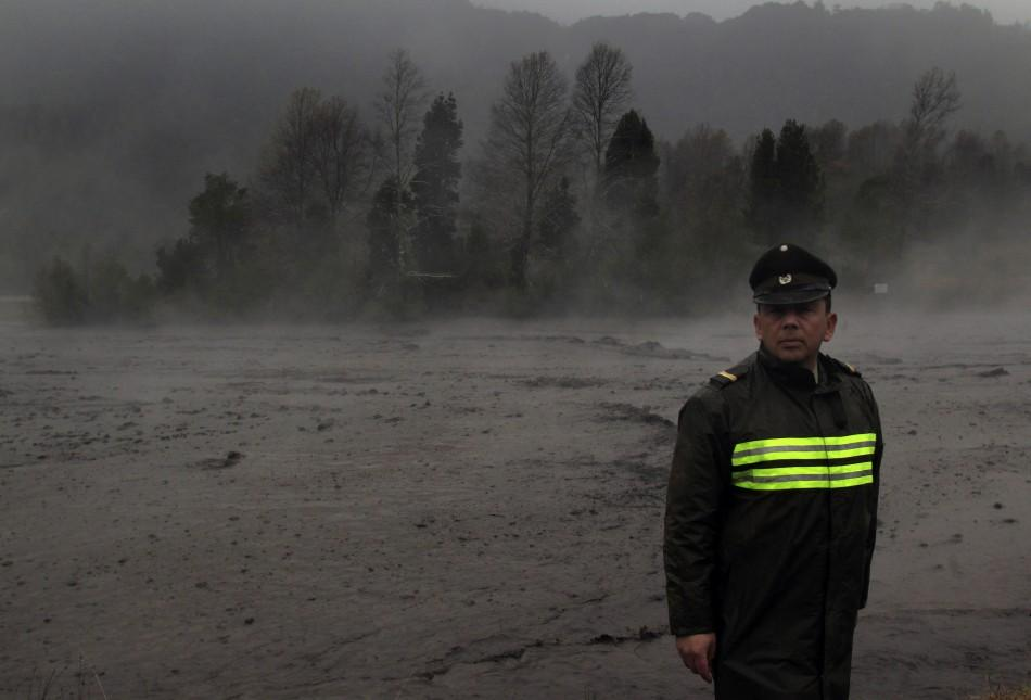 Steam rises from the Nilhue River, fed by unusually warm water from the hot flanks of an erupting volcano from the Puyehue-Cordon Caulle volcanic chain, as a policeman stands on the river bank near Lago Ranco town