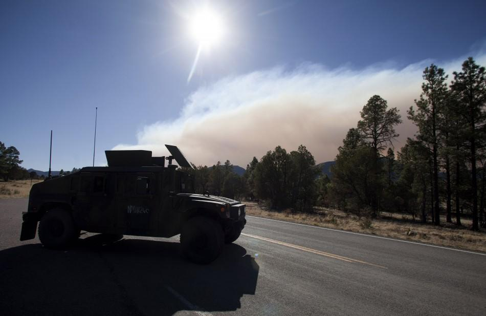 A National Guard vehicle travels on Highway 180 as smoke rises from the Wallow Wildfire outside Luna, New Mexico