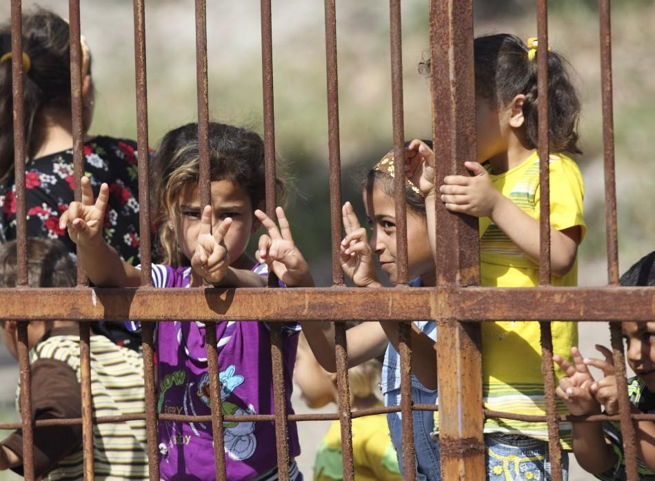 Syrian refugee children pose at a refugee camp in the Turkish border town of Yayladagi in Hatay province