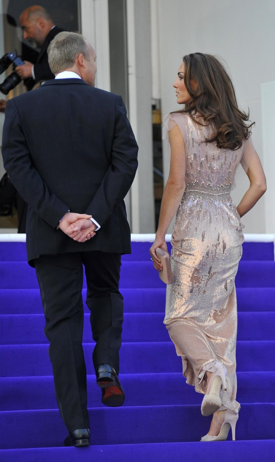 Britain's Catherine, Duchess of Cambridge walks up a staircase as she arrives with Prince William (not pictured) for a charity dinner at Kensington Palace in London June 9, 2011.