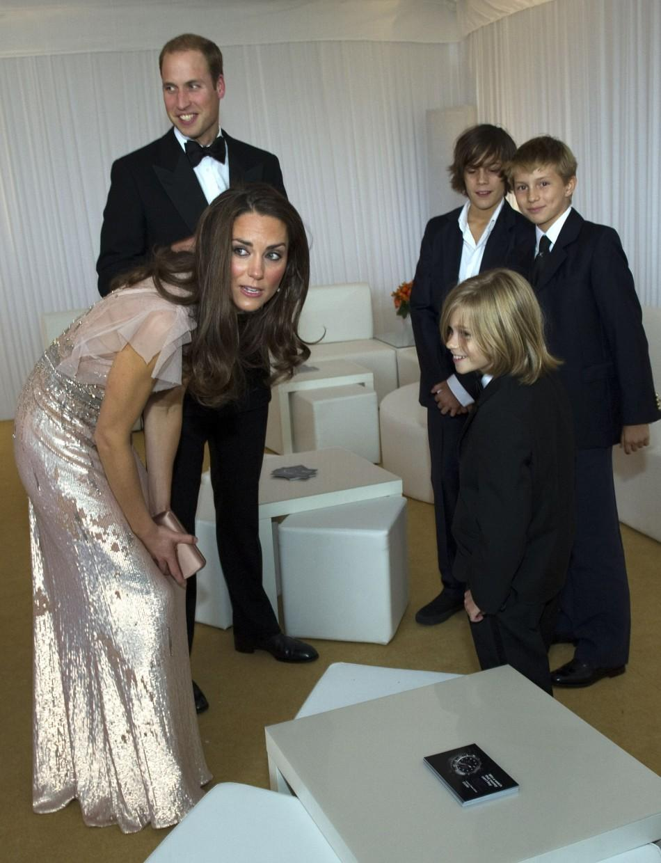 Britain's Prince William and his wife Catherine, Duchess of Cambridge speak with children as they arrive at the10th annual ARK (Absolute Return for Kids) gala dinner at Kensington Palace in London June 9, 2011.