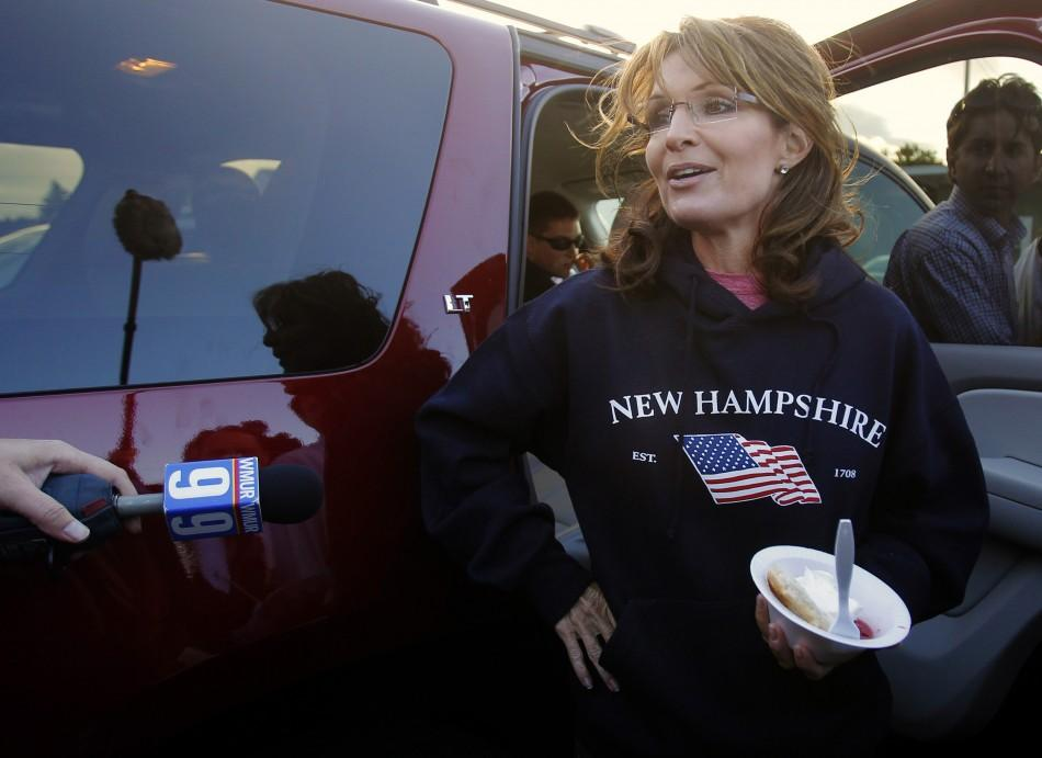 Former Alaska Governor Sarah Palin, wearing a New Hampshire sweatshirt, talks to reporters following a stop at a clam bake at a private residence in Seabrook