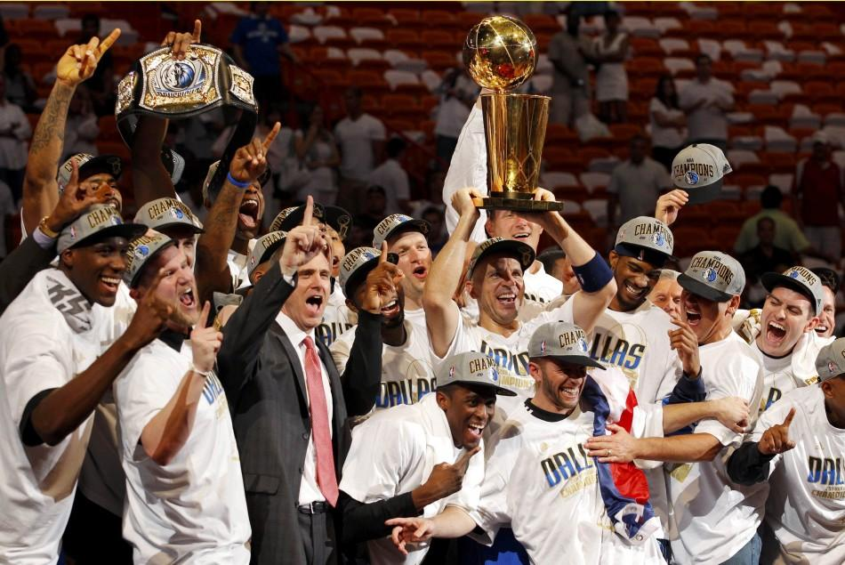 Dallas Mavericks' Jason Kidd raises the Larry O'Brien Championship Trophy surrounded by his teammates after the Mavericks beat the Miami Heat in Game 6 to win the NBA Finals basketball series in Miami.