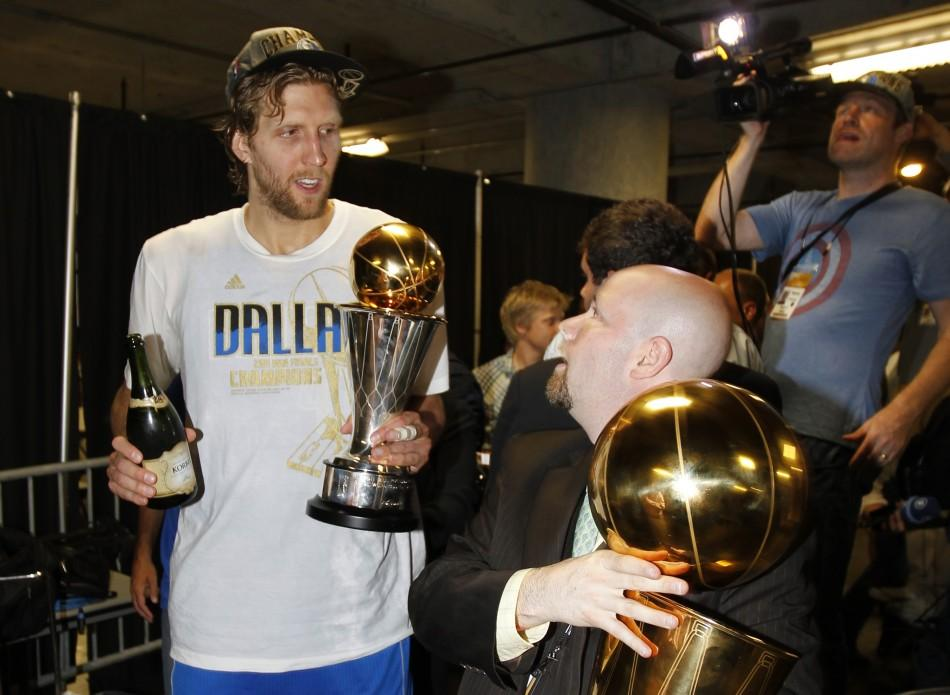 Dallas Mavericks Dirk Nowitzki walks with his MVP trophy and a bottle of champagne after the Mavericks won the NBA Championship defeating the Miami Heat in Miami