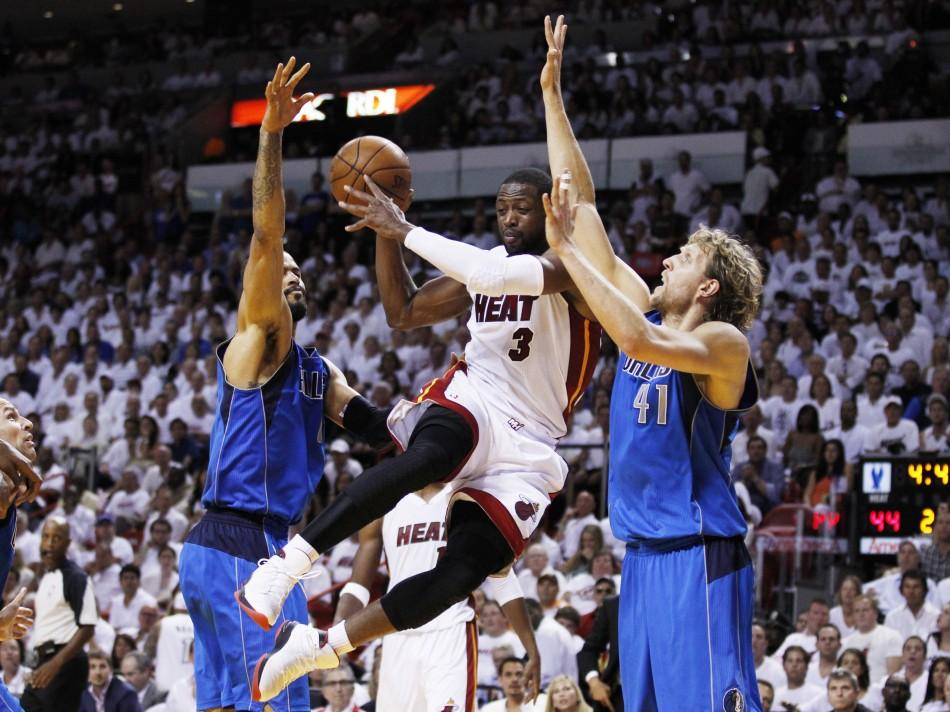 Heat's Wade drives between Mavericks' Chandler and Nowitzki during Game 6 of the NBA Finals basketball series in Miami
