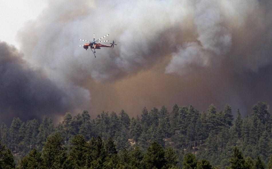 A heavy helicopter returns to Luna Lake after dropping water on a flair up north of the lake, on the eastern edge of the Wallow Wildfire outside Alpine