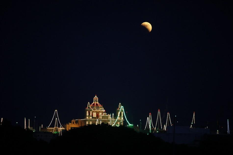 A partial lunar eclipse is seen over the village of Zejtun, lit up for its parish church feast of Saint Catherine, in the south of Malta
