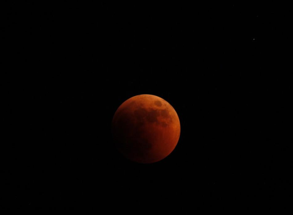 A full lunar eclipse is seen from the village of Marsascala in the south of Malta