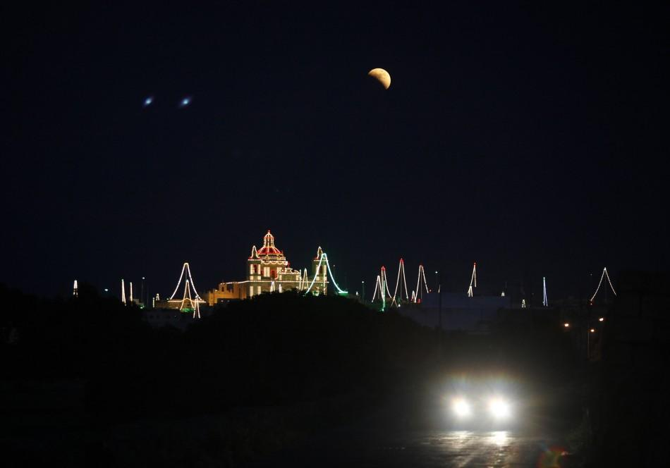 A partial lunar eclipse is seen over the village of Zejtun, lit up for its parish church feast of Saint Catheri