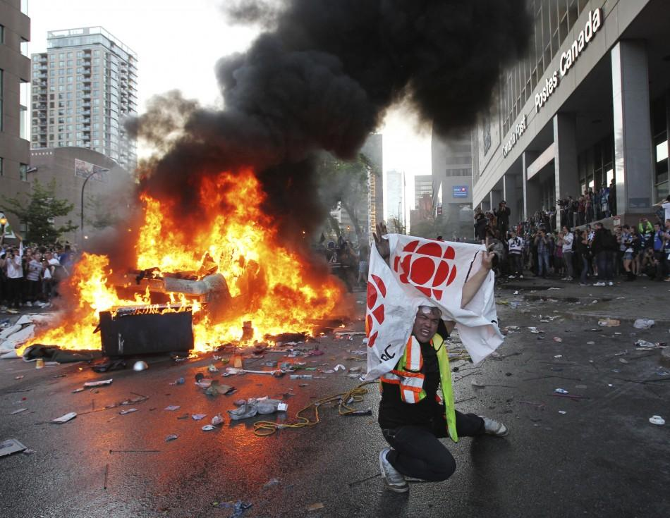 A Canucks fan waves in front of an overturned burning pickup truck in downtown Vancouver, British Columbia during riots after the Canucks lost the NHL Stanley Cup playoffs to the Bruins