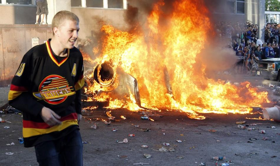 A Canucks fan stands in front of a burning vehicle during riots in Vancouver, British Columbia after the Canucks lost the NHL Stanley Cup final hockey game to the Bruins