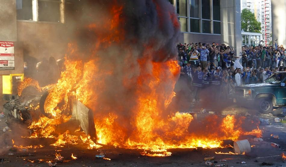 A vehicle burns as Canucks fans react to their team's loss to the Bruins in the NHL Stanley Cup final hockey game in Vancouver
