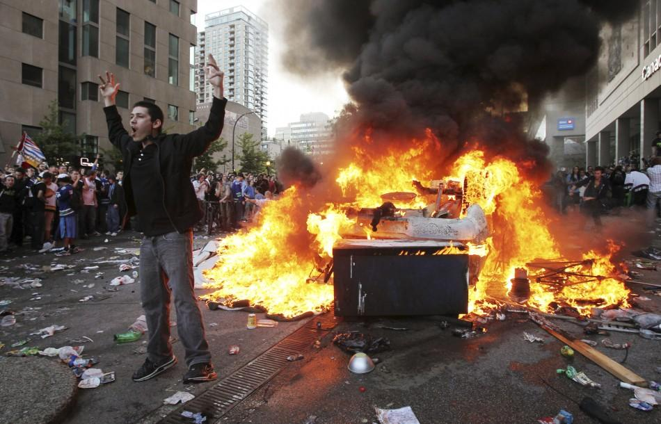 A Canucks fan screams in front of an overturned burning pickup truck in downtown Vancouver, British Columbia during riots after the Canucks lost the NHL Stanley Cup playoffs to the Bruins