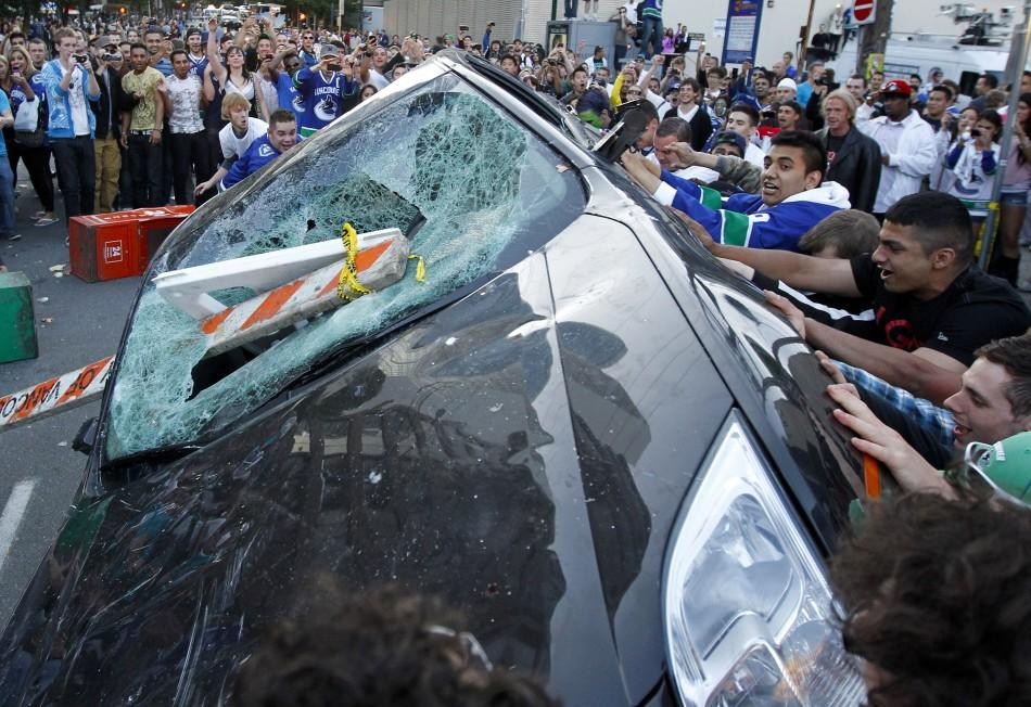 Canucks fans push over a vehicle as they react to their team's loss to the Bruins in the NHL Stanley Cup final hockey game in Vancouver