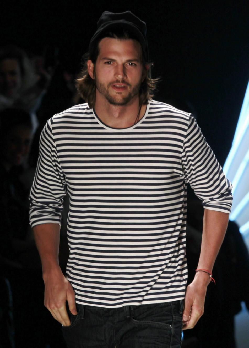 U.S. actor Ashton Kutcher presents a creation from Colcci's Summer 2012 collection during Sao Paulo Fashion week