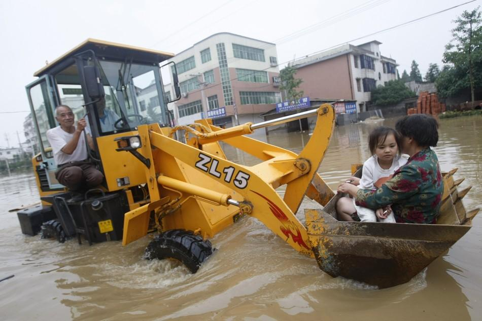 A rescuer transfer an elderly woman and her granddaughter with an excavator on a flooded street in Xianning