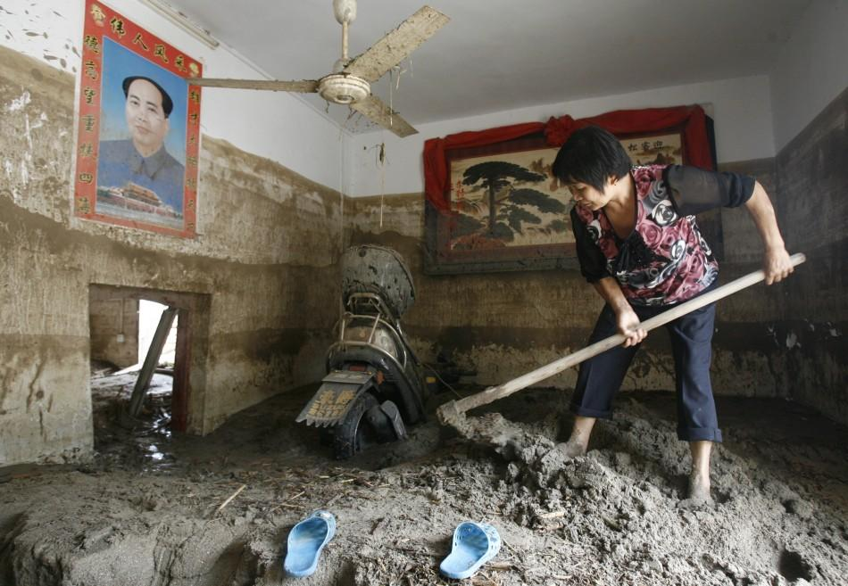 A woman shovels mud at her house after a landslide triggered by heavy rainfalls in Linxiang