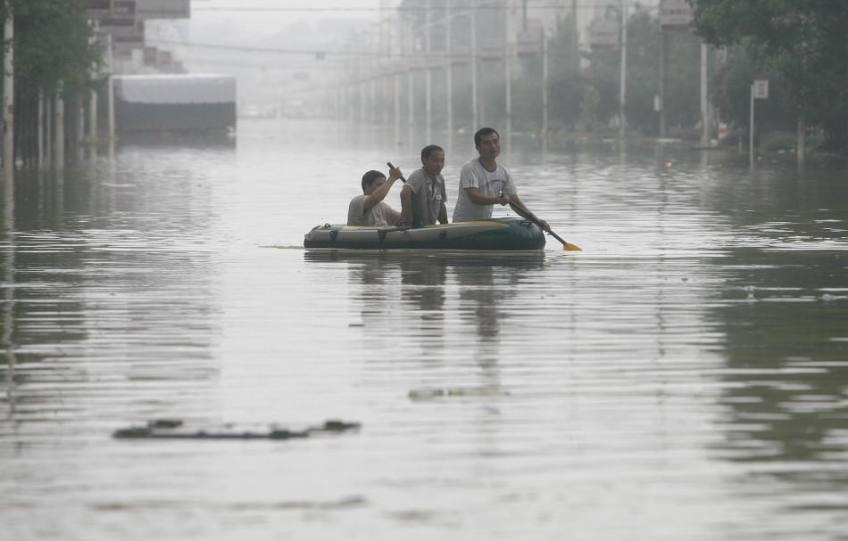 Residents row their rubber dinghy past a flooded street in Xianning