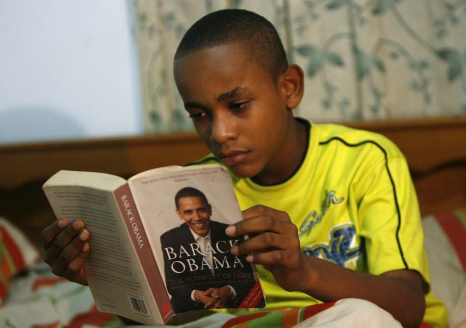 Felix Agyaba Afriyie, who resembles U.S President Barack Obama and was reported on local TV, reads book at his home in Accra