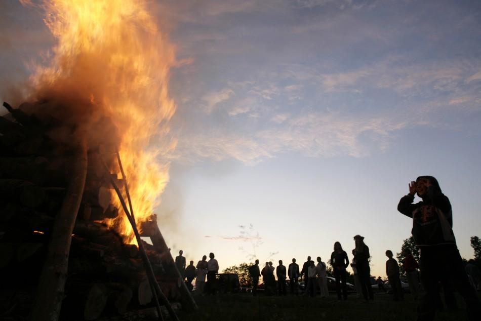 Locals observe a bonfire as they celebrate summer solstice in Tuja, about 75 km (47 miles) from the capital Riga