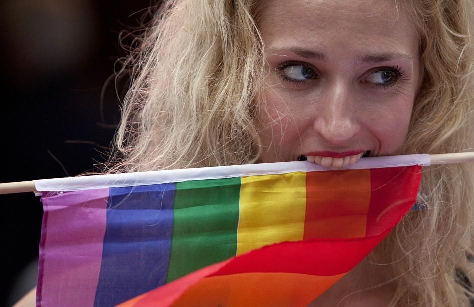 A protester clenches a rainbow flag with her teeth at a demonstration outside Sheraton Hotel where U.S. President Obama was attending a function in New York.