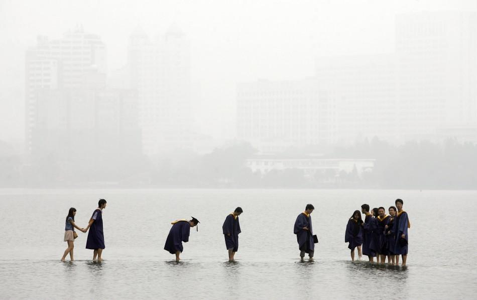 Students in graduation robes stand on a stone bridge submerged underwater at the flooded Donghu Lake in Wuhan, Hubei province, June 21, 2011.