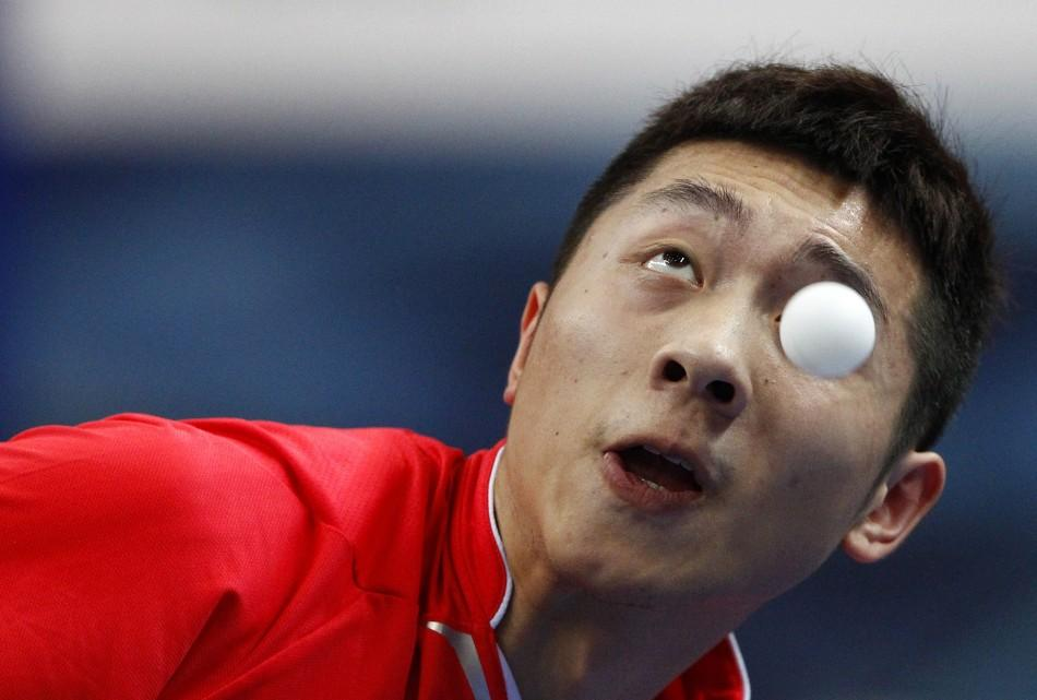 China's Xu eyes the ball as he serves against Boll of Germany during their table tennis game at the Volkswagen 2011 China vs. World Team Challenge event in Shanghai