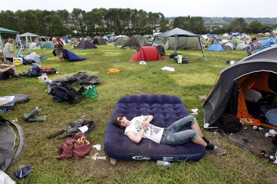 A festival goer sleeps on an inflatable matress before leaving Worthy Farm and the Glastonbury Festival inSomerset June 27, 2011.