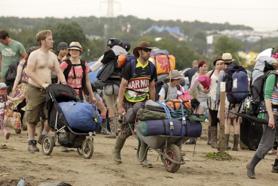Festival goers leave Worthy Farm and the Glastonbury Festival in Somerset June 27, 2011.