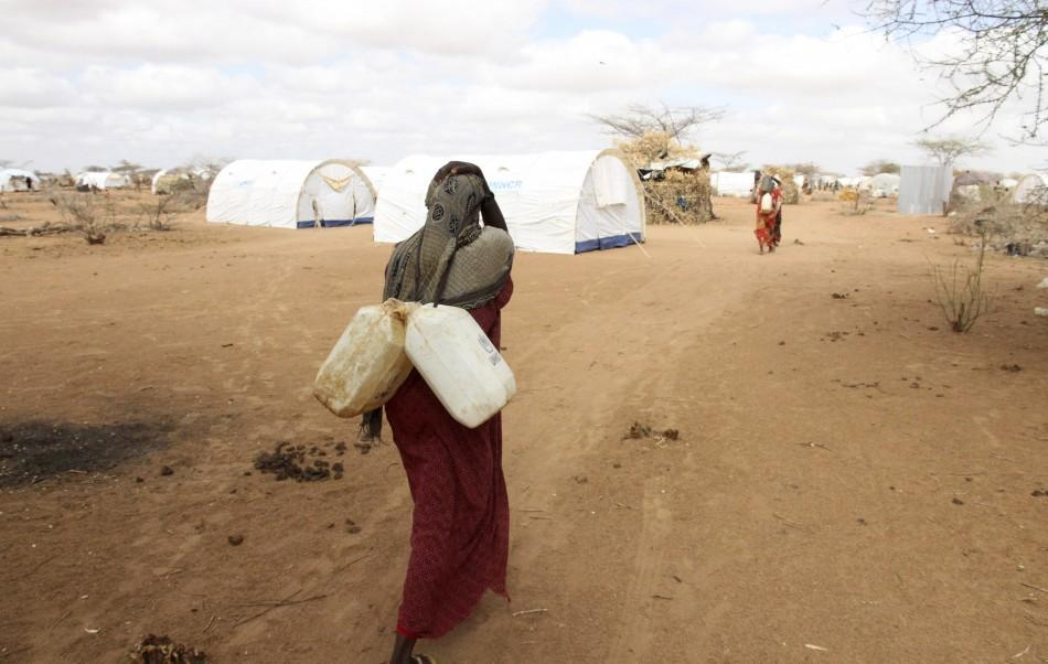 A Somali refugee carries jerry-cans of water from a tap at the Dagahaley camp in Dadaab