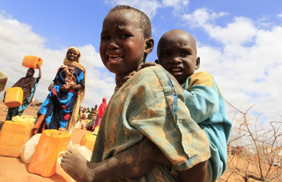 A Somali refugee child who recently arrived at the Dagahaley camp cries while carrying a sibling, in Dadaab