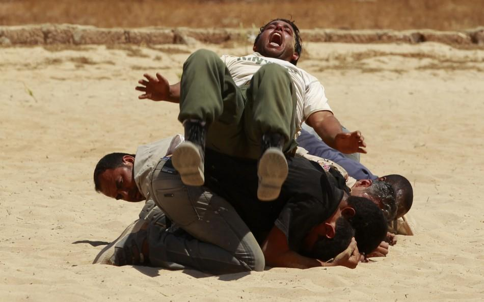 Rebel fighters demonstrate their skills during their graduation ceremony in Benghazi
