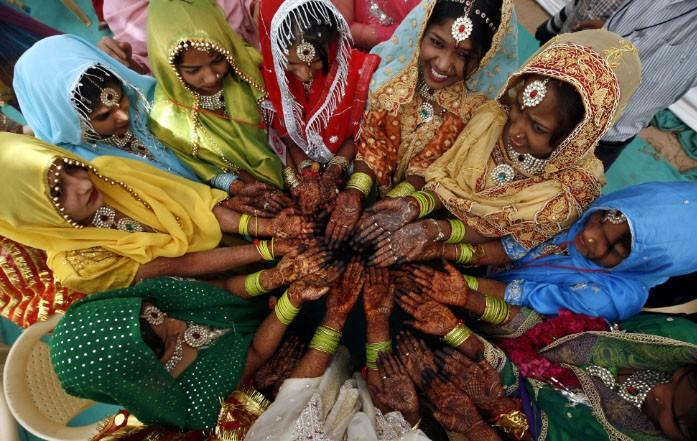 Muslim brides show their hands decorated with henna paste as they wait for the start of a mass marriage ceremony in the western Indian city of Ahmedabad March 6, 2011