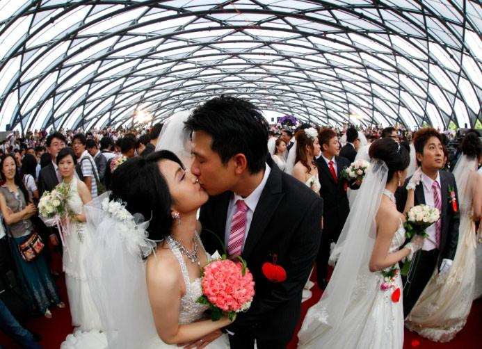 Zheng Ya-yuan (L), 32, and Chang Hong-chang, 31, who have been dating for six years, kiss during a mass wedding ceremony at the Taipei Flora Expo Hall September 9, 2010